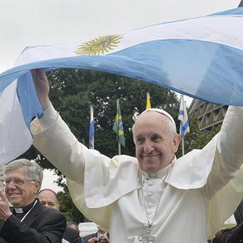 Pope Francis holds up an Argentine flag outside the Metropolitan Cathedral in Rio de Janeiro, Brazil (AP)