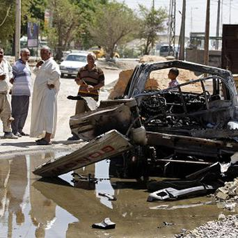 Civilians inspect the aftermath of a car bomb attack in Baghdad (AP)