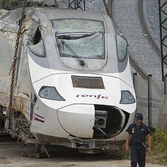 Police stand guard as the wreckage of the crashed train is seen ready to be moved in Santiago de Compostela (AP)