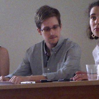 Edward Snowden, centre, at a news conference in Sheremetyevo Airport, Moscow, with Sarah Harrison of WikiLeaks, left (AP)