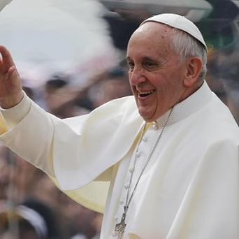 Pope Francis waves from his popemobile along the Copacabana beachfront on his way to celebrate Mass (AP)