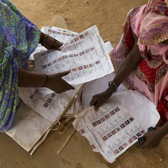 Voters look for their names on voter lists scattered on the ground at the main polling place in Kidal, Mali (AP)