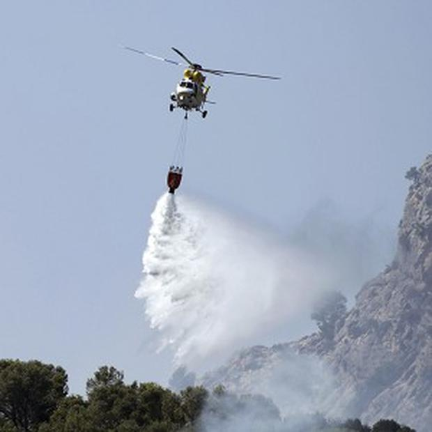 A helicopter works above a fire, near the village of Andratx on the Spanish Balearic island of Majorca (AP)