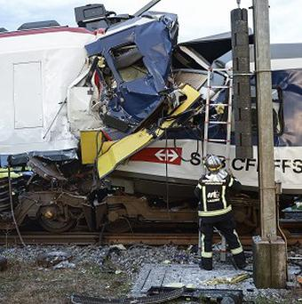 A fireman works at the site where two passenger trains collided head-on in Granges-pres-Marnand, western Switzerland (AP/Keystone)