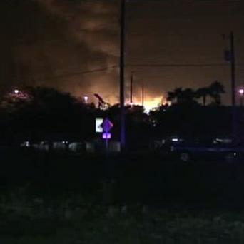 Flames are seen in the distance rising above a gas plant in Tavares, Florida, following a series of explosions (AP)