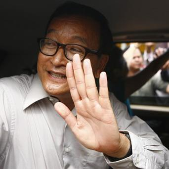 President of Cambodia's National Rescue Party Sam Rainsy waves to his party supporters from his car after attending a public forum (AP)