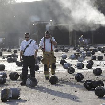 Firefighters walk through an area of exploded propane cylinders in the aftermath of blasts and a fire at a gas company (AP)