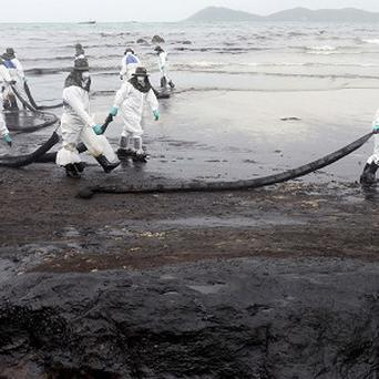 Workers remove crude oil during a clean up operation on the beach of Prao Bay on Samet Island (AP)