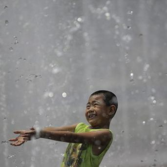 A boy cools off in a fountain at a park in Shanghai (AP)
