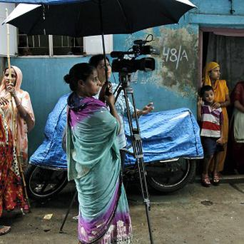 Neighbors of Badar Azim, the 25-year-old footman who gained international fame by helping to announce the birth of Prince George, gather at the entrance of his house in Kolkata (AP)