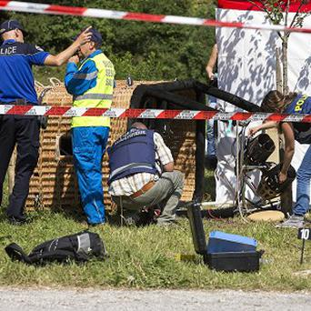 Swiss police inspect the gondola of a hot air ballon after it crashed in Montbovon, killing an American father (AP)