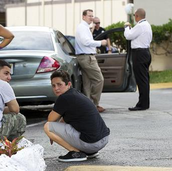 Two people sit behind a police car as Miami police officers investigate a killing in Miami (AP)