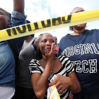 Relatives overcome with emotion as they wait to be reunited with their children after a shooting at a school near Atlanta (AP)
