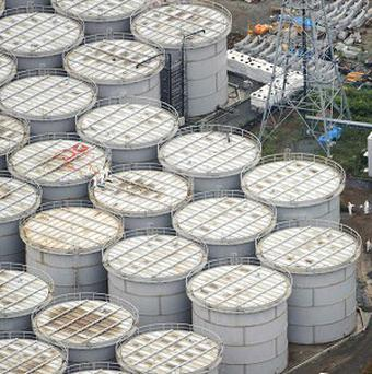 Workers stand on storage tanks at the Fukushima Dai-ichi nuclear plant (AP/Kyodo News)
