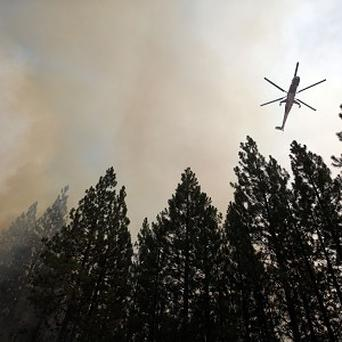 A helicopter drops water over a hot spot while battling the Rim Fire near Yosemite National Park, California (AP)