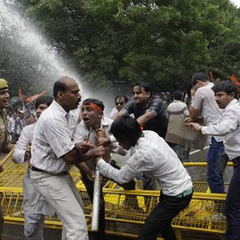 Hindu protesters are hit with a police water cannon (AP)