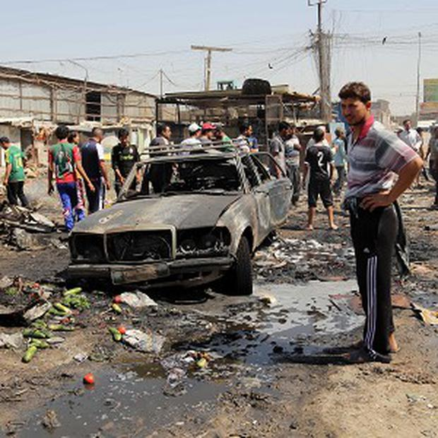 People inspect the site of a car bomb attack at a vegetable market in the Jamilah area of Baghdad on Wednesday (AP)