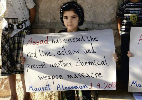 A Syrian girl holds a sign during a demonstration in Maaret al-Numan, Idlib province, northern Syria