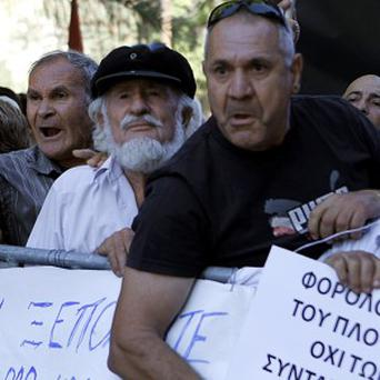 Demonstrators at an anti-bailout protest outside the parliament in capital Nicosia (AP)