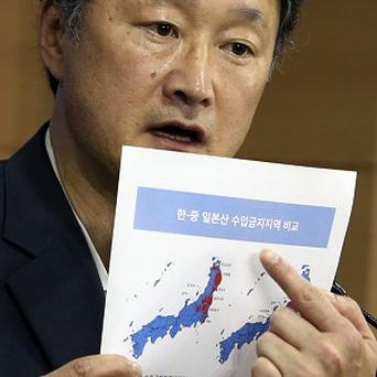 Son Jae-hak, vice minister of South Korean Maritime Affairs and Fisheries, with a document showing Japanese prefectures with import bans (AP)