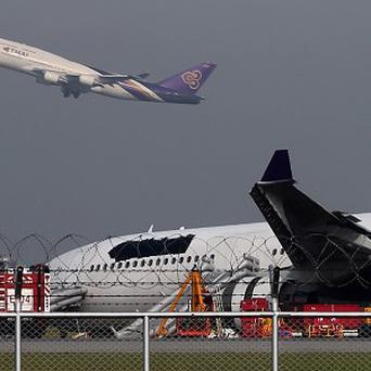 A passenger plane takes off over a damaged Thai Airways Airbus A330-300 after it skidded off the runway in Bangkok (AP)
