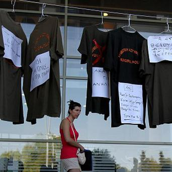 A woman walks past a display by protestors of municipal police T-shirts with written signs, one reading 'We want jobs, not joblessness' in the city of Thessaloniki (AP)
