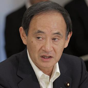 Japan's Chief Cabinet Secretary Yoshihide Suga says the French newspaper cartoon insults those affected by the March 2011 disaster at the Fukushima nuclear plant (AP)