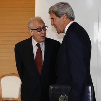 US Secretary of State John Kerry, right, greets the UN Special Representative for Syria Lakhdar Brahimi in Geneva (AP)