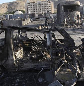 Security personnel investigate the site of a suicide car bombing near the US consulate in Herat (AP)