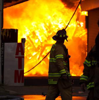 A New Jersey firefighter walks near a store in flames during a massive fire in Seaside Park in New Jersey on September 12