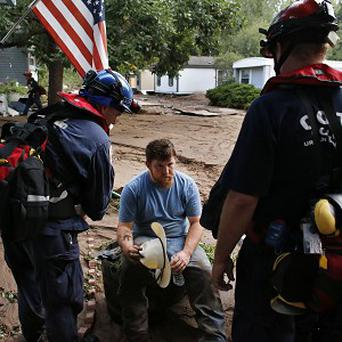 A local resident gets help from emergency responders after floods left homes and infrastructure in a shambles in Colorado (AP)