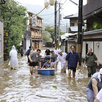 Hotel guests get a boat ride through a flooded street after torrential rains caused by a powerful typhoon in Kyoto (AP/Kyodo News)