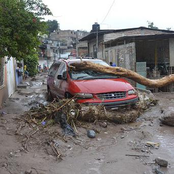 A damaged vehicle stands in the middle of a road after a landslide caused by heavy rains came down on a neighbourhood in Chilpancingo (AP)