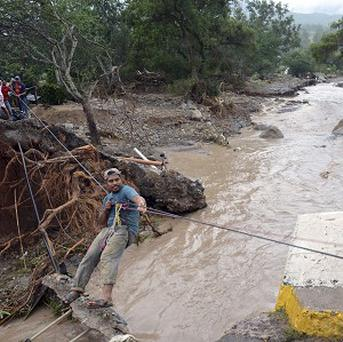 A man uses a makeshift zip line to cross a river after a bridge collapsed near the town of Petaquillas, Mexico (AP)