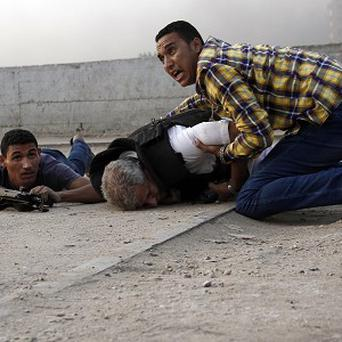 Egyptian security forces try to help Giza Police Gen Nabil Farrag, who died after militants opened fire on security forces (AP/Ahmed Abdel Fattah)