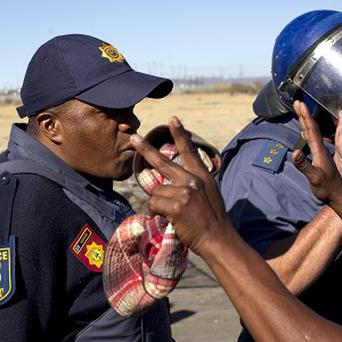 Police officers attempt to stop mine workers from marching towards the mine before a memorial service (AP)