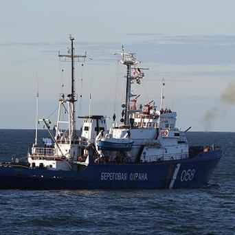 A Russian Coast Guard vessel fires a warning shot as activists attempts to climb an oil platform in Russia's Pechora Sea (AP /Denis Sinyakov, Greenpeace)