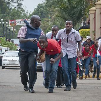 Civilians who had been hiding inside during gunbattles manage to flee from the Westgate Mall in Nairobi (AP)