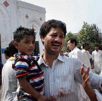People mourn over the death of a relative at the site of suicide attack on a church in Peshawar, Pakistan (AP)