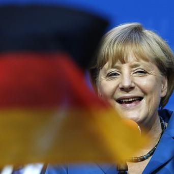 Chancellor Angela Merkel smiles behind German flags at the party headquarters in Berlin (AP)