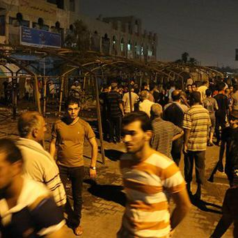 People inspect the site of a suicide bomb attack in the Shiite neighbourhood of Sadr city in Baghdad, Iraq (AP)