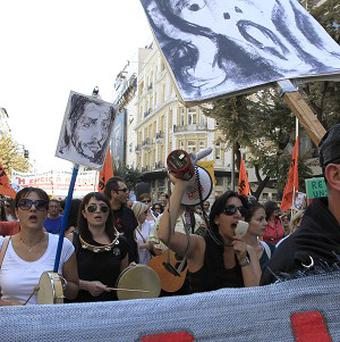 Teachers hold placards and chant slogans during a protest against job cuts in Greece (AP)