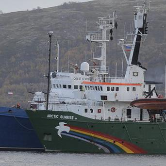 Greenpeace ship Arctic Sunrise is escorted into harbour by a Russian coast guard boat (AP)