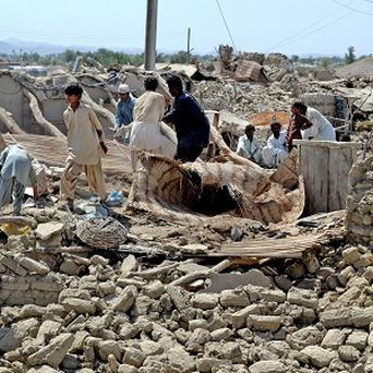 Pakistani villagers look for belongings amid the rubble of their destroyed homes following an earthquake in the remote district of Awaran (AP)