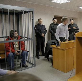 Greenpeace activist Roman Dolgov, left, sits in a cage during a hearing in a courtroom in Murmansk, Russia (AP)