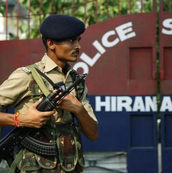An Indian paramilitary soldier stands guard outside the site of an attack at a police station in Hiranagar (AP)