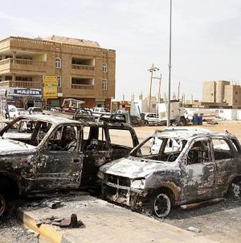 Destroyed cars are left after rioters torched a petrol station in Khartoum, Sudan (AP)