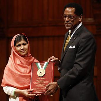 Malala Yousafzai is presented with the 2013 Peter J Gomes Humanitarian Award by Dr Allen Counter, director of the Harvard Foundation and professor of neurology at Harvard Medical School.