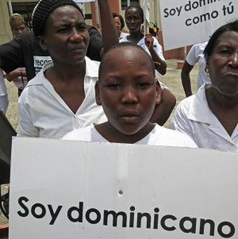 A youth of Haitian descent holds a sign that reads in Spanish