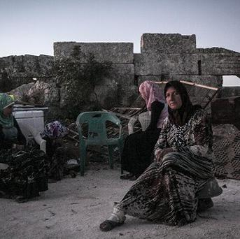 Displaced Syrian women sit among ruins used as a temporary shelter near Kafer Rouma in Syria's Idlib province (AP)